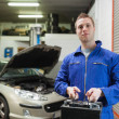 Confident auto mechanic with car battery — Stock Photo #24093793