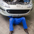 Stock Photo: Male mechanic lying under car