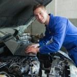 Mechanic using laptop on car engine — Stock Photo