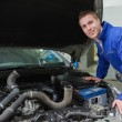 Mechanic working under car bonnet - Stock Photo