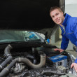 Stock Photo: Mechanic working under car bonnet