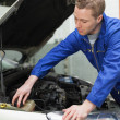 Stockfoto: Mechanic closing lid of windshield washer tank