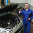 Mechanic by car showing thumbs up sign — Stock Photo