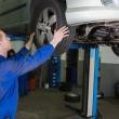 Auto mechanic examining car tire — Stock Photo
