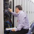 Technician with a clipboard checking servers - Stock Photo