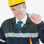 Mature repairman looking through wrench — Stock Photo #24094357