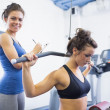 Smiling trainer with woman using weights machine — Stock Photo
