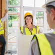 Woman smiling at architect while man is measuring — Stock Photo