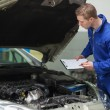 Stock Photo: Mechanic checking car engine