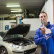 Mechanic offering spanner in worshop - Foto de Stock