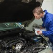 Mechanic with clipboard examining car engine — Стоковая фотография