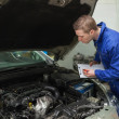Mechanic with clipboard examining car engine — Stock Photo #24094653