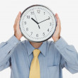 Businessman holding clock in front of face - Stock Photo
