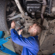 Repairman examining under car — Stock Photo