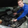 Happy mechanic with laptop repairing car — Stock Photo #24094731
