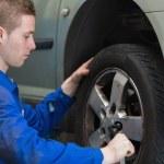 Male mechanic changing car wheel — Stock Photo #24094781