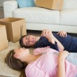 Couple lying on the floor with their moving boxes - Stock Photo