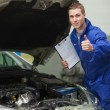 Mechanic by car showing thumbs up — Stock Photo #24094943