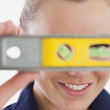 Female technician holding spirit level — Stock Photo