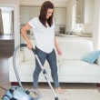 Woman standing at the living room hoovering — Stock Photo #24095015