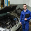 Confident mechanic standing by car with open hood — Stock Photo #24095063