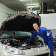 Mechanic by car giving thumbs up gesture — Stock Photo #24095113
