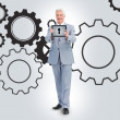 Stock Photo: Businessmstanding against cogs background
