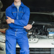 Happy mechanic leaning on breakdown car — Stockfoto