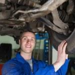 Male mechanic examining car tire — Stock Photo