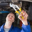 Mechanic repairing car with adjustable pliers — Stock Photo #24095521