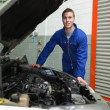 Happy mechanic standing by car - Stock Photo