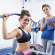 Smiling woman on weights machine with trainer — Stock Photo #24096021
