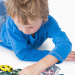 Close-up of boy playing with playhouse and toy cars — Stock Photo #24096033