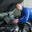 Male auto mechanic using laptop — Foto Stock