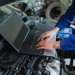 Auto mechanic using laptop - Stock Photo