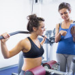 Trainer with woman on weights machine — Stock Photo
