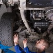 Stock Photo: Mechanic working under car