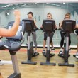 Enthusiastic woman teaching spinning class — Stock Photo #24096357