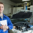 Happy car mechanic with tablet pc — Stock Photo