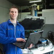 Auto mechanic working on laptop - Stock Photo