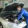 Stock Photo: Mechanic examining car engine