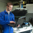 Mechanic using laptop - Stock Photo
