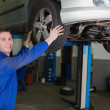 Stock Photo: Auto mechanic adjusting car tire