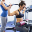 Female trainer with client on weights machine — Stock Photo