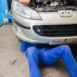 Auto mechanic working under car — Stock Photo