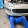Auto mechanic working under car — Stock Photo #24097089