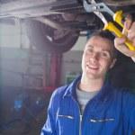 Happy male mechanic repairing car — Stock Photo