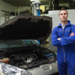 Confident auto mechanic by car — Stock Photo