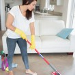 Woman mopping the living room floor — Stock Photo