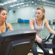 Two women working out on exercise bikes — Stock Photo